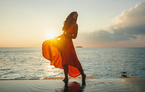Woman at a beach resort during sunset