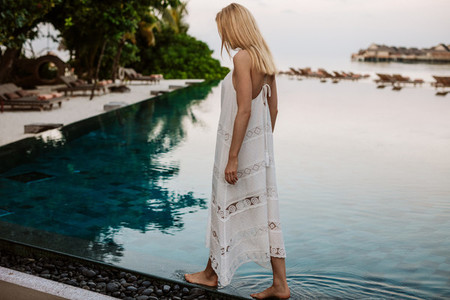 Woman tourist at an infinity pool