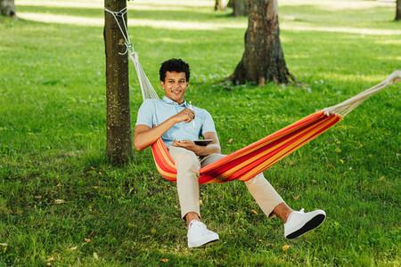 Smiling guy sitting on hammock