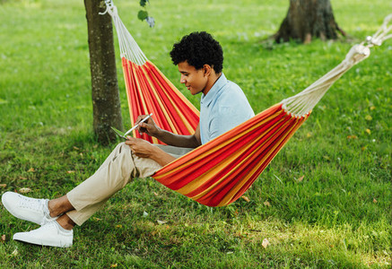 Young man sitting on hammock