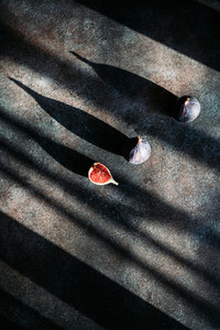 Creative abstract food photography of fresh ripe cutted figs on the textured background with sunlight and shadows