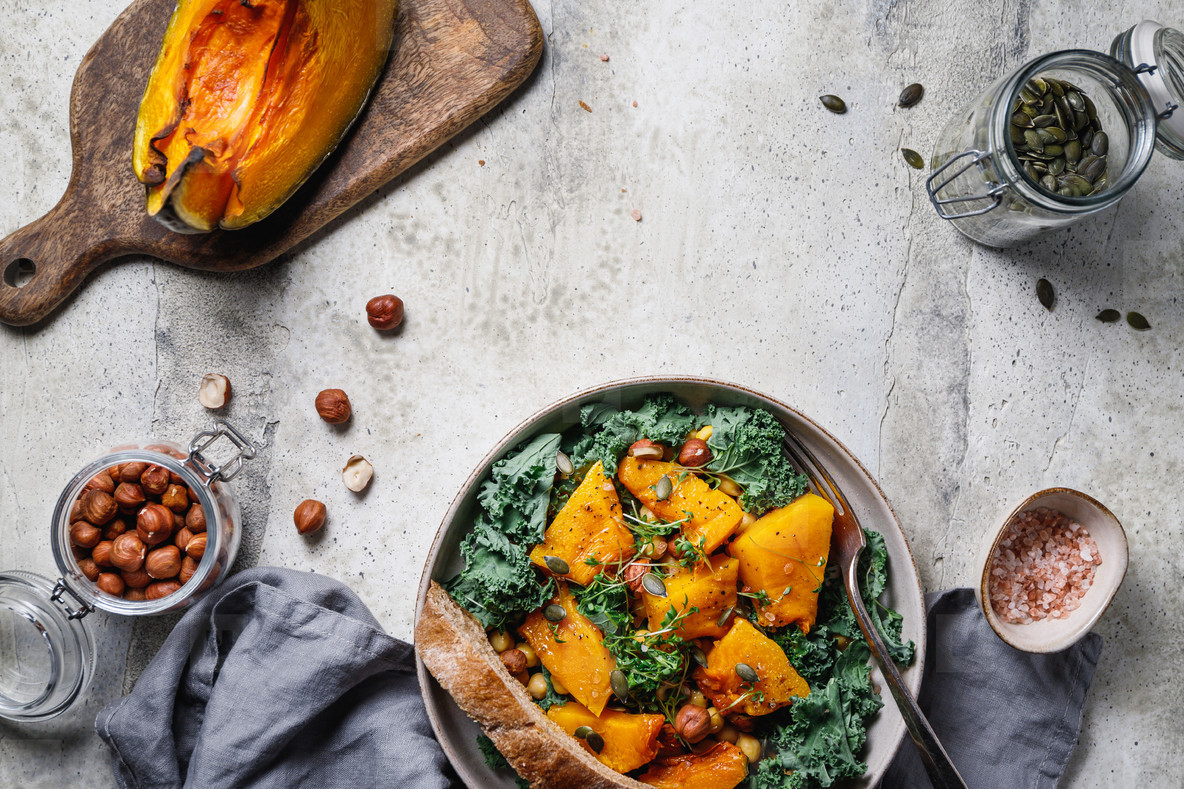 Season salad with grilled pumpkin  kale  chickpea  pepitas and nuts  Autumn vegetarian healthy recipe  top view  copy space