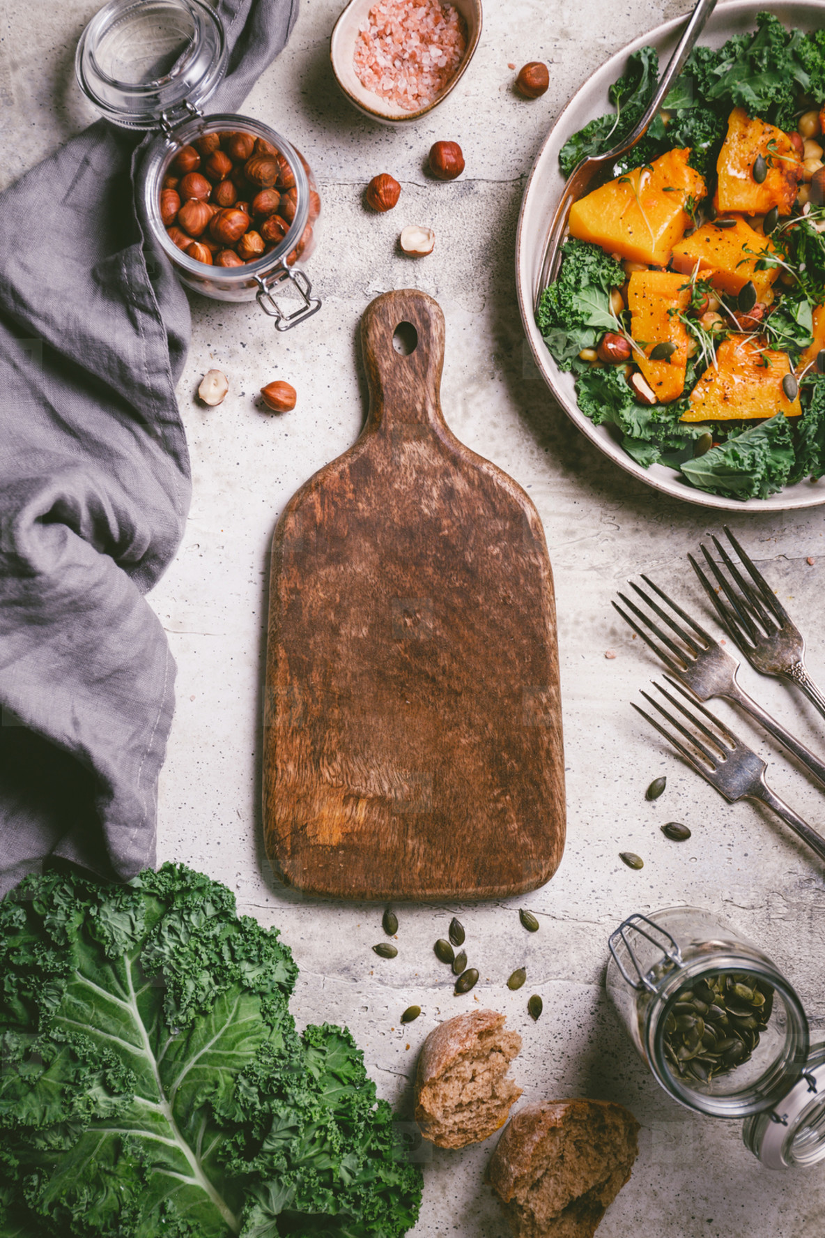Empty wooden cutting board surrounded seasonal fall products Roasted pumpkin salad  kale  bread  nuts and seeds  Top view  food frame background
