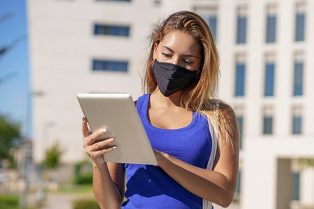 Young woman wearing a mask uses digital tablet outdoors