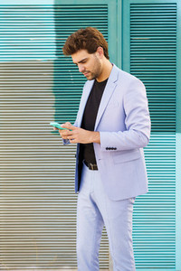 Young man wearing a suit texting with smartphone outdoors
