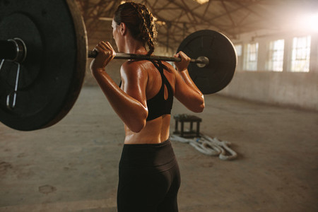 Woman doing squats with barbell