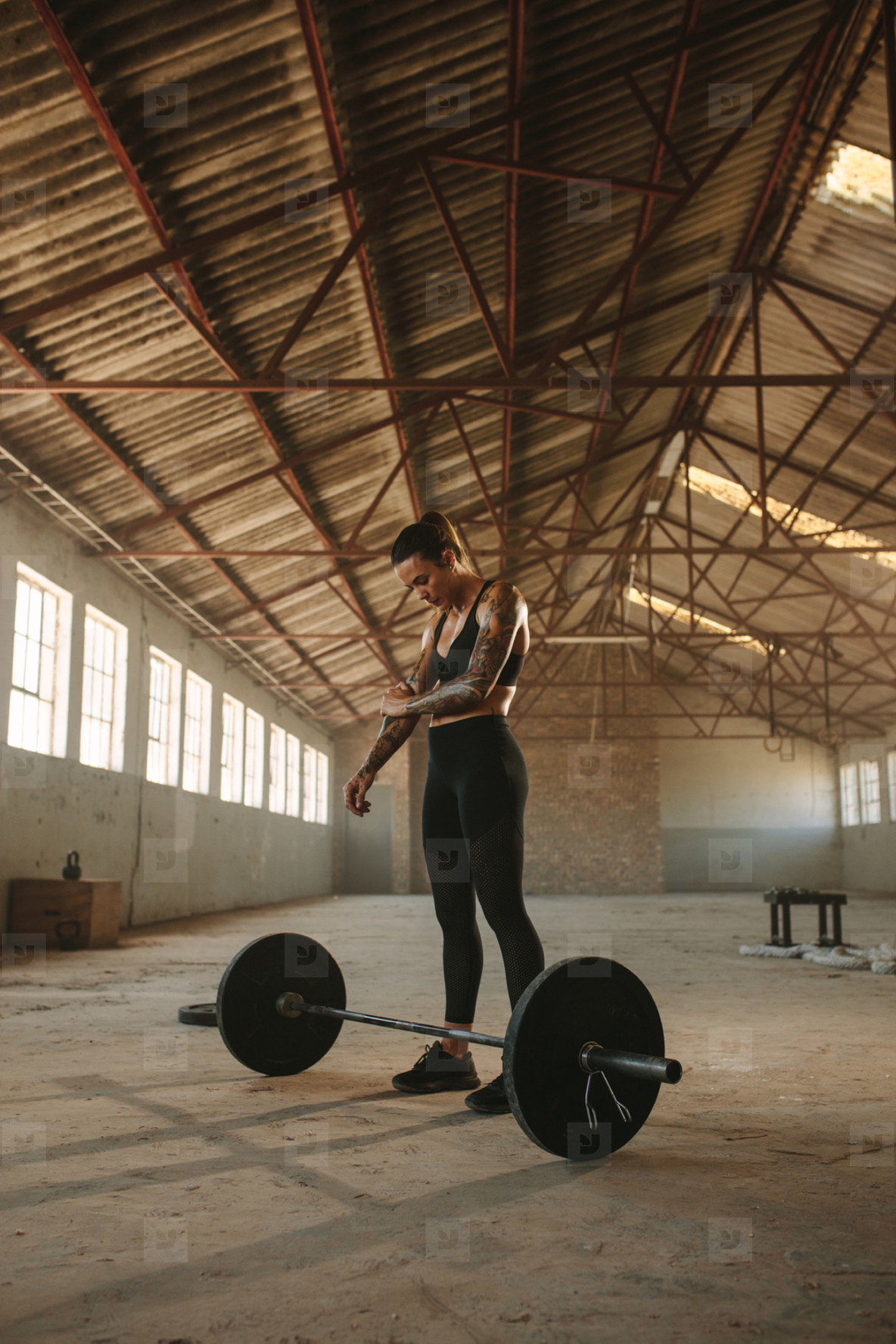 Fitness woman exercise with barbell in old warehouse