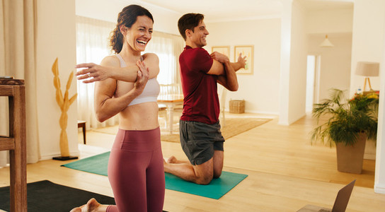 Smiling couple exercising together at home