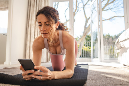 Woman perform yoga on mat using online session