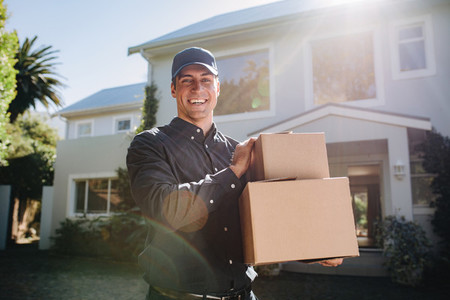 Smiling delivery person with parcel boxes