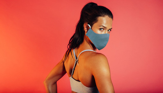 Fitness woman in a face mask glancing back