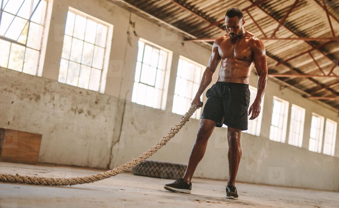 Man taking rest after battle rope workout