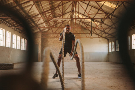 Strong man exercising with battle ropes