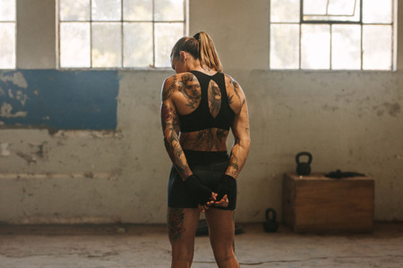 Tattooed woman boxer in old warehouse