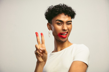 Gay man with smeared lipstick showing peace sign