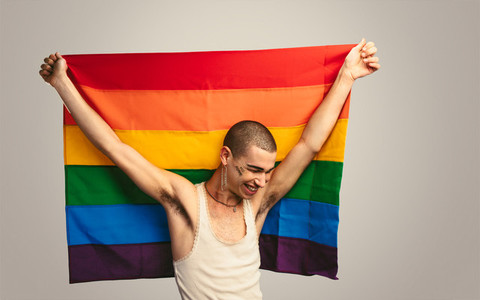 Gay man smiling with a lgbt flag