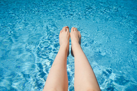White woman legs against a turquoise pool water