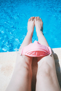 Woman legs in a swimming pool near a protective pink mask