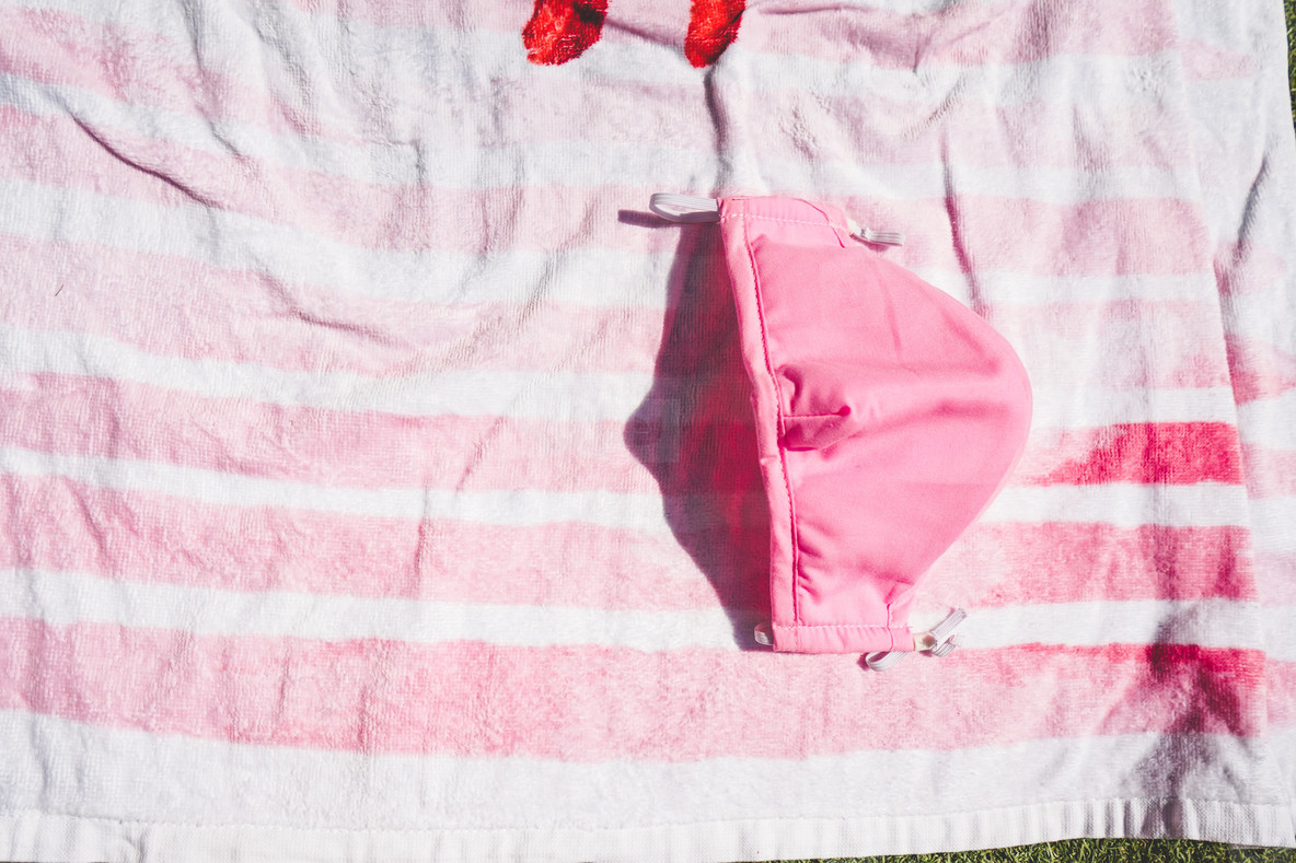 Pink face mask against a stripped pink towel