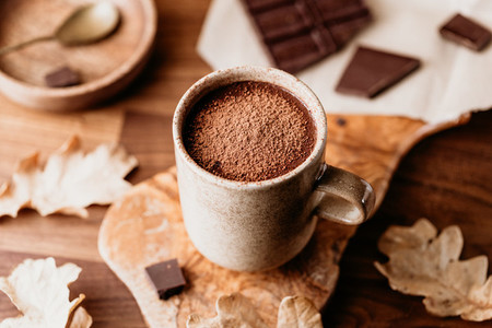 Close up of hot chocolate in a ceramic mug on the table  Autumn or winter cozy still life