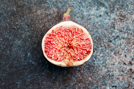Macro photography of a fresh ripe cutted fig on the textured background