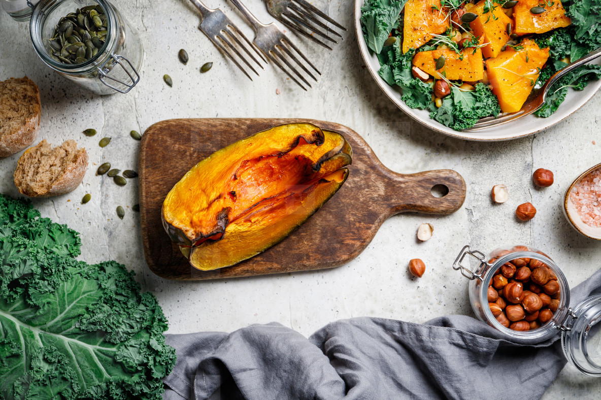 Roasted pumpkin on a wooden cutting board surrounded fall seasonal products  Kale  bread  nuts and seeds  Top view  food frame background