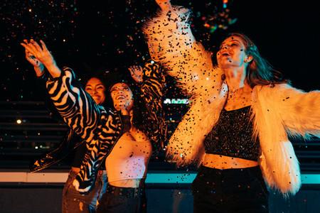 Happy girls throwing confetti