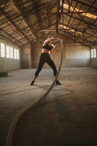 Strong woman using training ropes for exercise