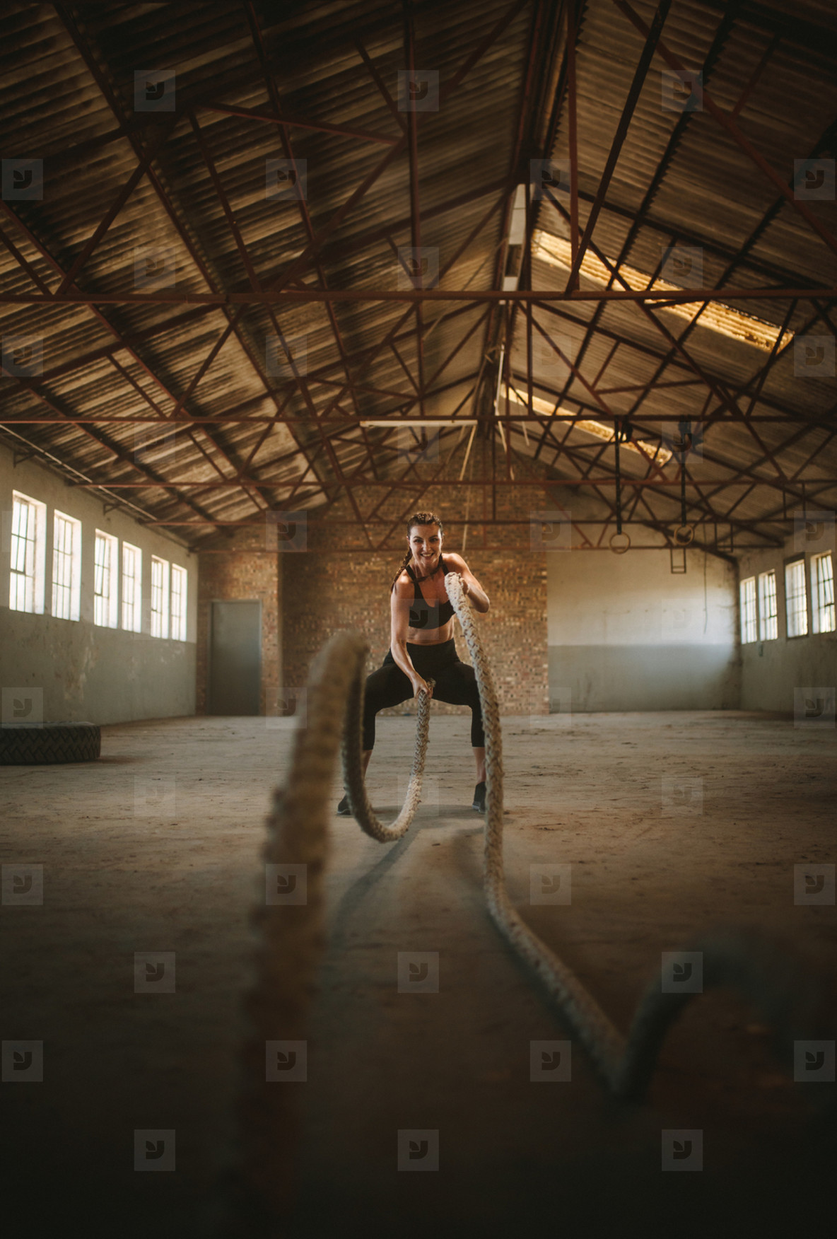 Tough female working out with battling ropes