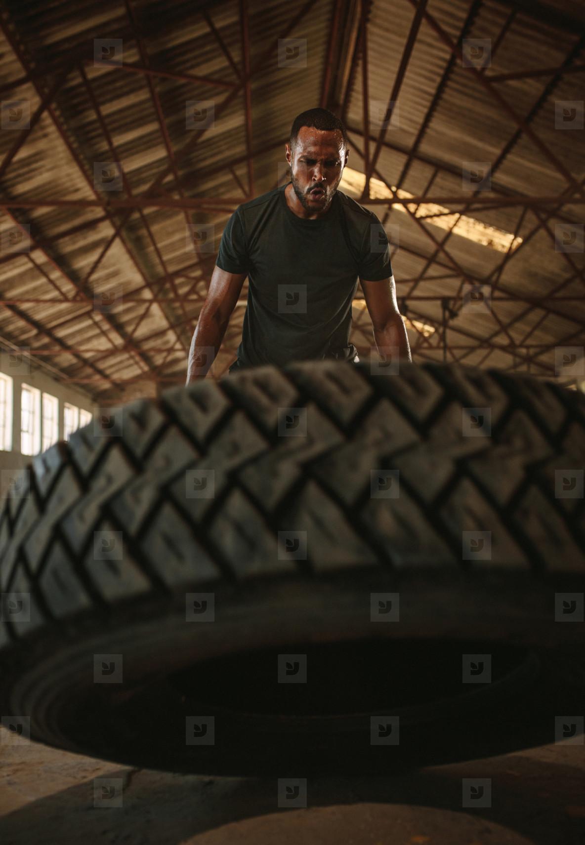 Muscular man doing cross training inside old warehouse
