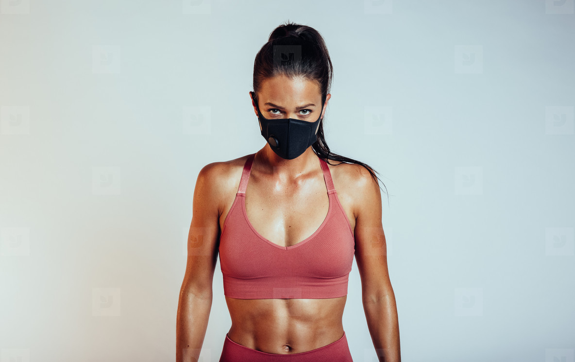 Woman with muscular build in face mask