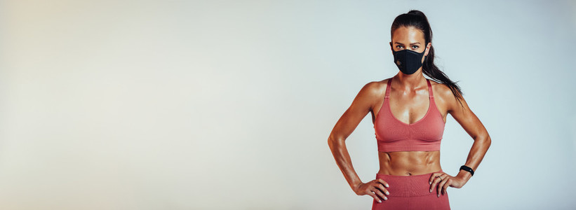 Muscular female in sportswear and face mask