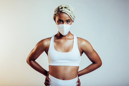 Fitness woman with face mask standing on white background