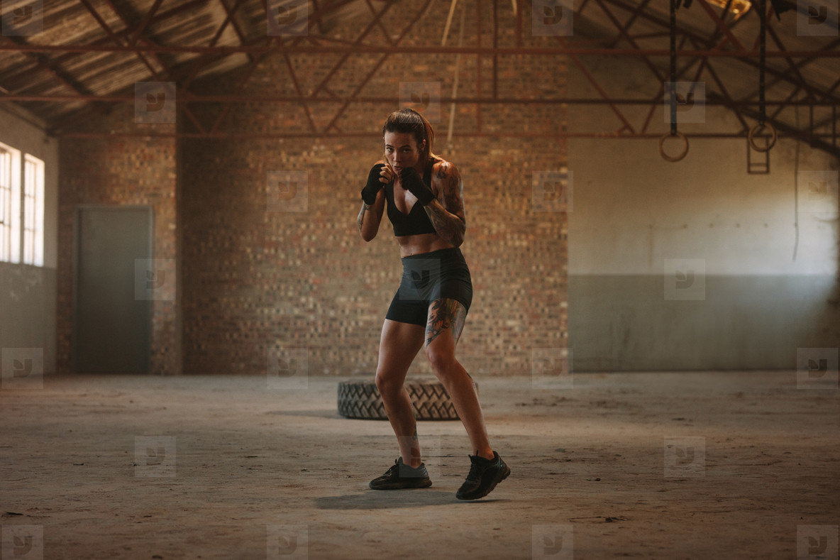 Woman shadow boxing in empty factory shade