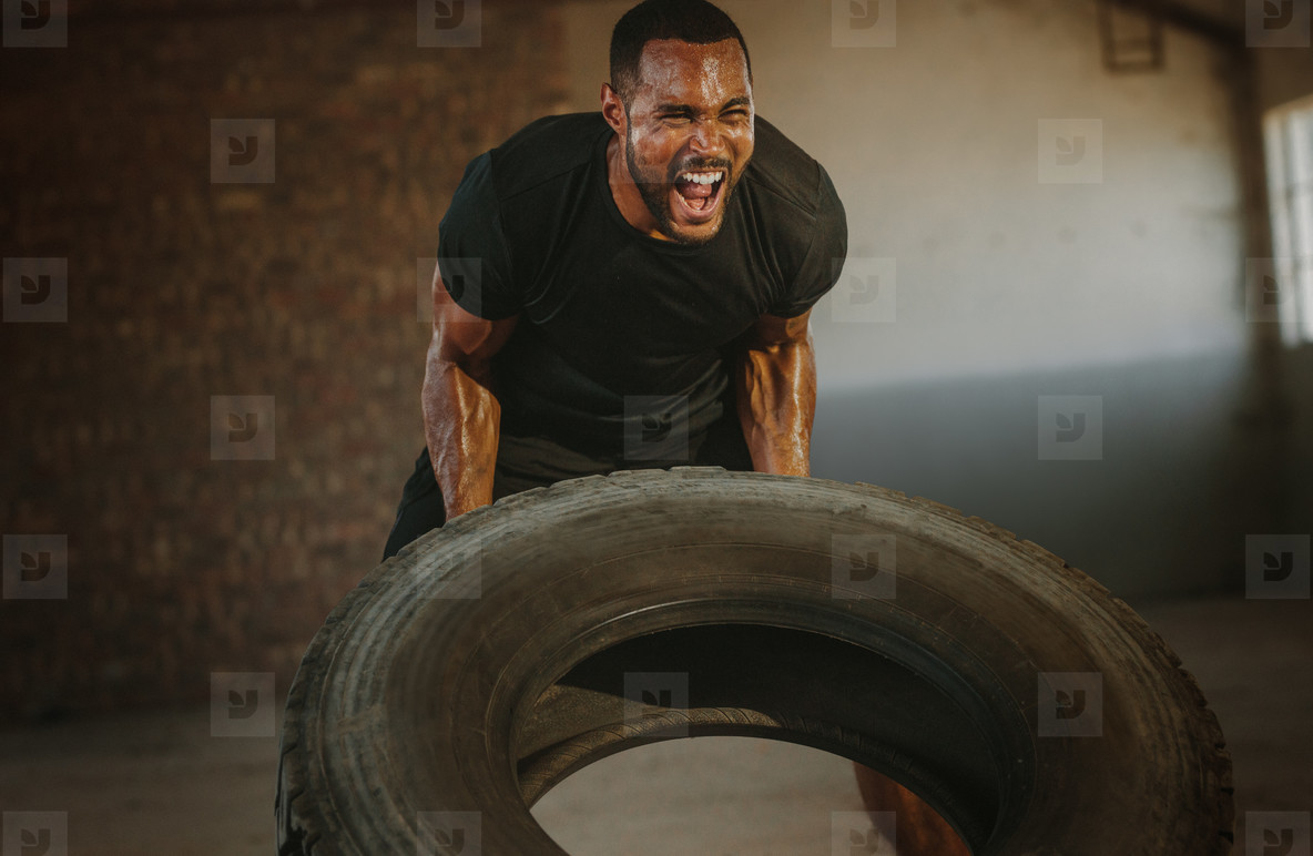 Strong man doing heavy tire flip exercise