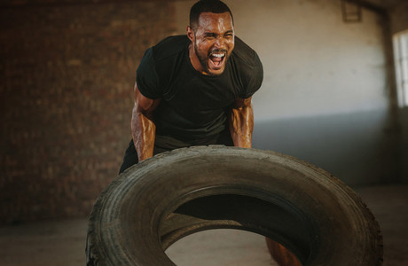 Strong man doing heavy tire flip exercise