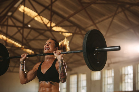 Bodybuilder woman doing weight lifting workout