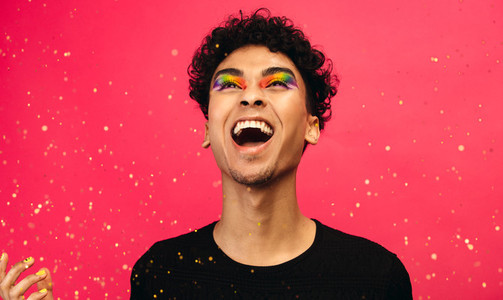 Excited gay man with glitters