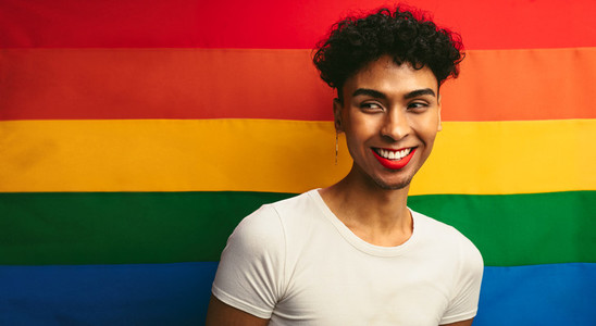 Gay man smiling against pride flag