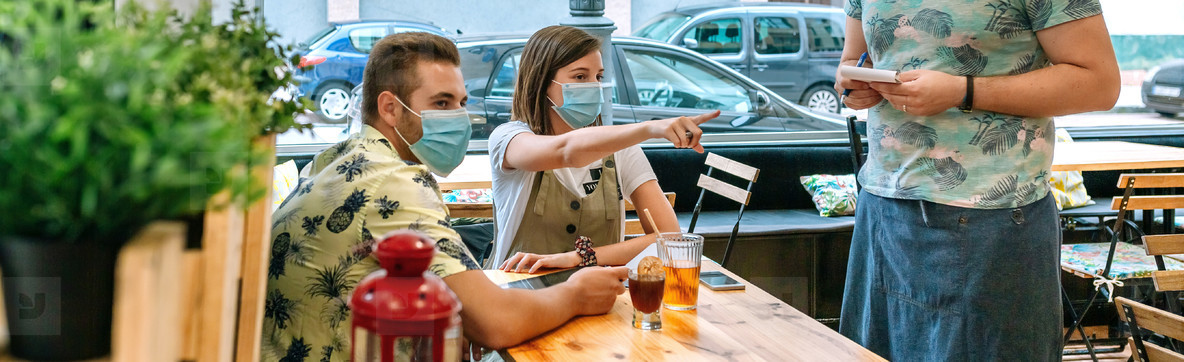 Couple with mask making food order to waiter