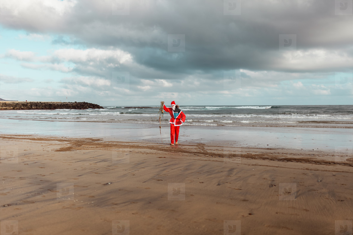 Man cleaning the beach of plastics and fishing nets