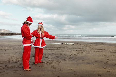 A couple dressed as santa claus on the beach