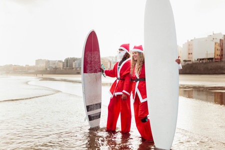 A couple dressed as santa claus on the beach with their surfboards