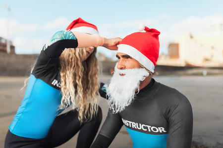 Couple on the beach help each other to dress up as Santa Claus