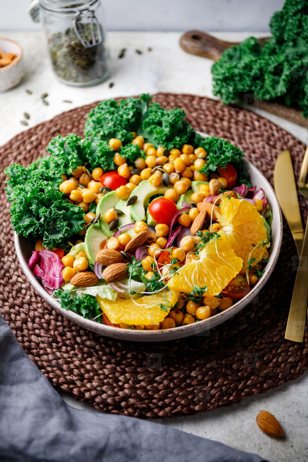 Healthy vegetarian salad with avocado  chickpea  fresh kale  romano leaf  cherry tomatoes  almond  onion and orange