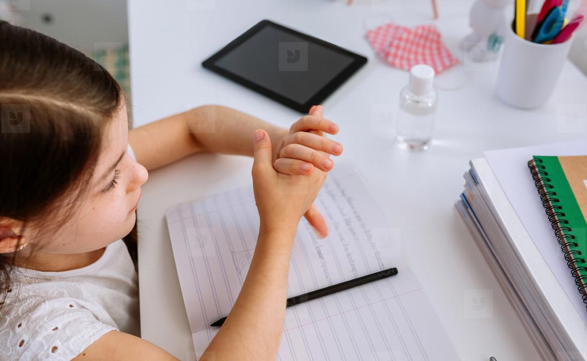 Girl applying hand sanitizer while doing homework