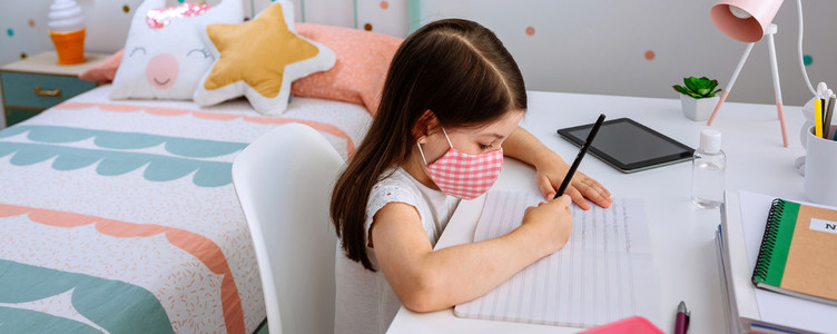 Girl with mask doing homework in her bedroom
