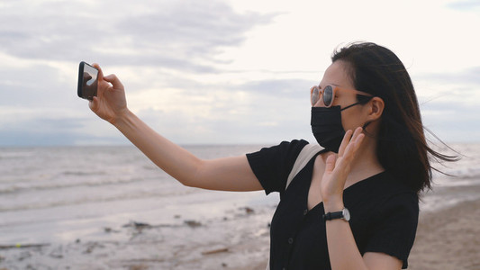 Young asian woman wearing medical mask and video call or facetim