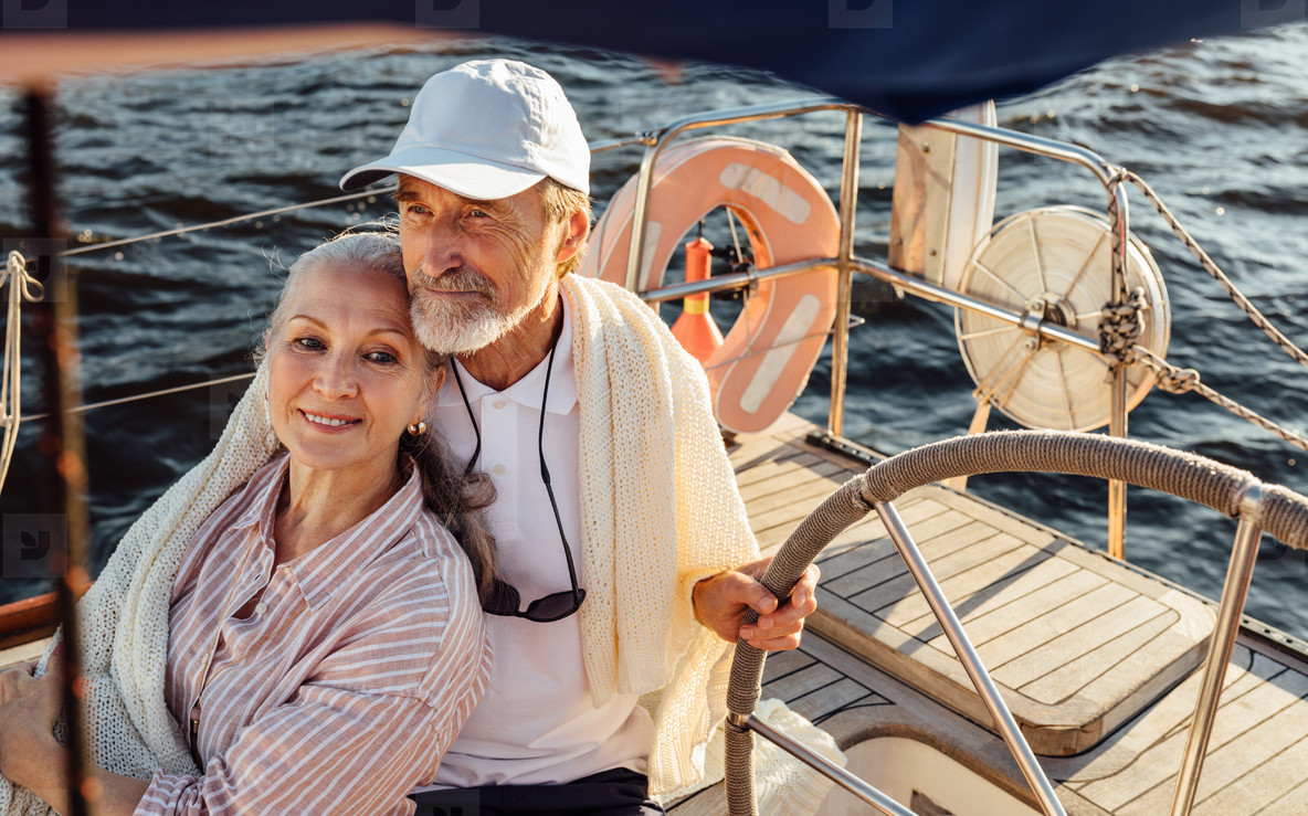 Mature couple sitting on yacht