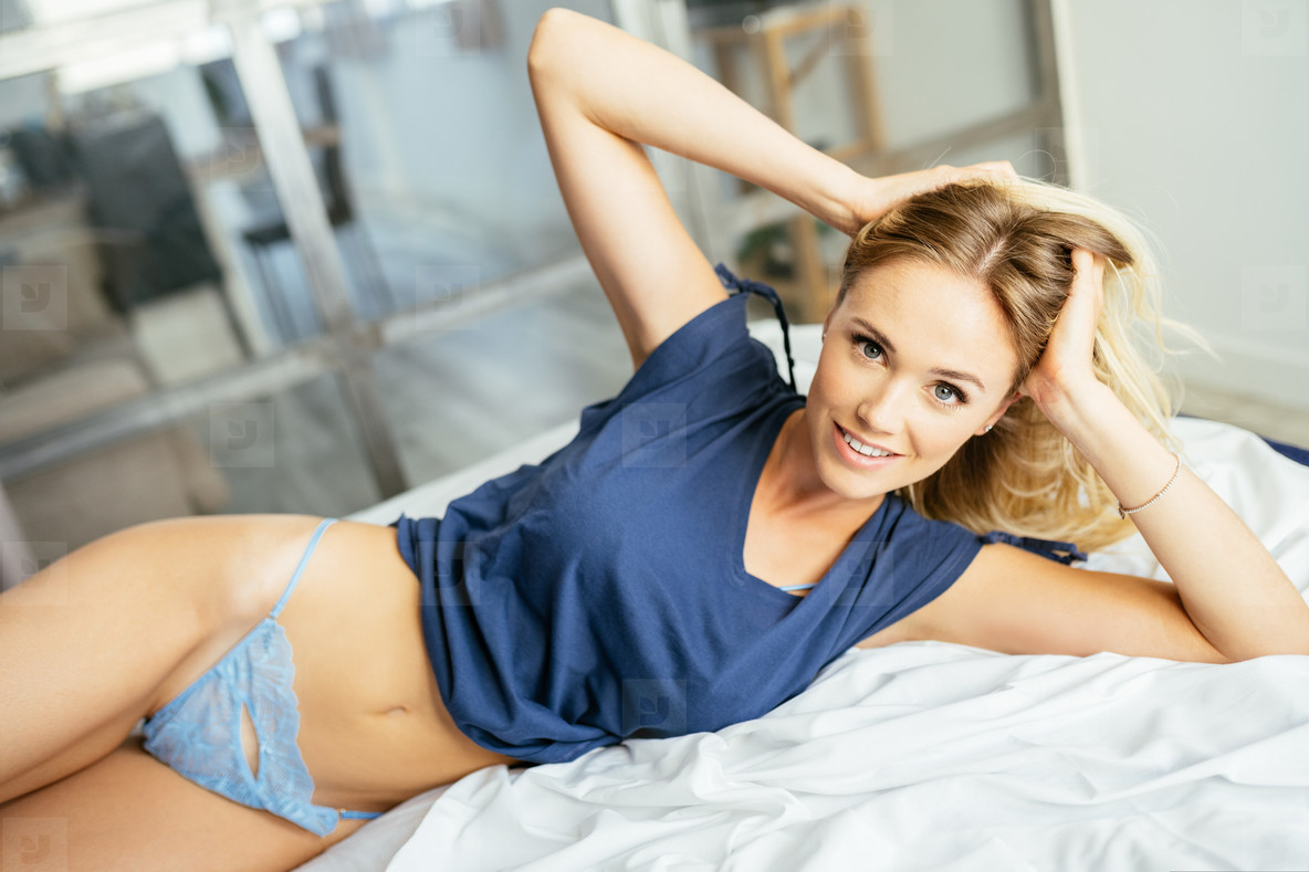 Caucasian girl posing in her bed wearing a blue t shirt and panties